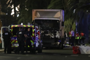 Police officers and rescued workers stand near a van that ploughed into a crowd leaving a fireworks display in the French Riviera town of Nice on July 14, 2016. The mayor of the French city of Nice said dozens of people were likely killed after a van rammed into a crowd marking Bastille Day in the French Riviera resort today and urged residents to stay indoors.  / AFP / VALERY HACHE        (Photo credit should read VALERY HACHE/AFP/Getty Images)