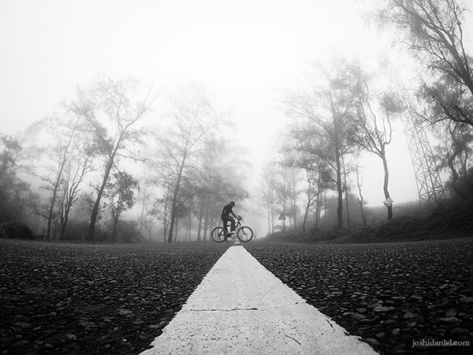 Black and white self-portrait of joshi daniel on a bicycle in the middle of the road in Ponmudi in Trivandrum, Kerala